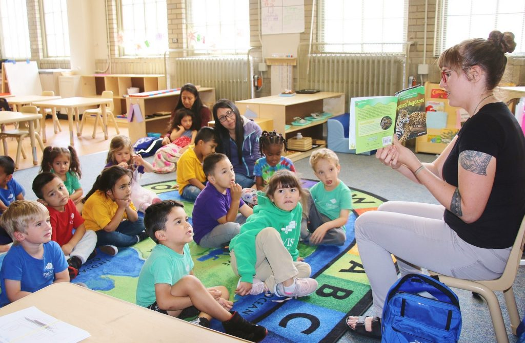 woman reading a book to kids, sitting on the floor in front of her